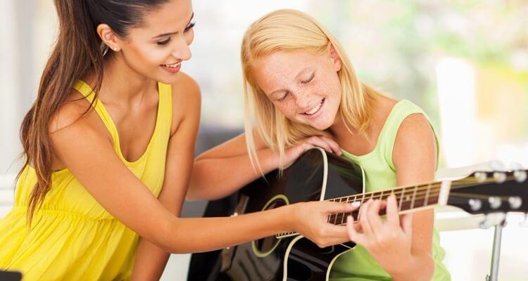 teacher-giving-guitar-lessons